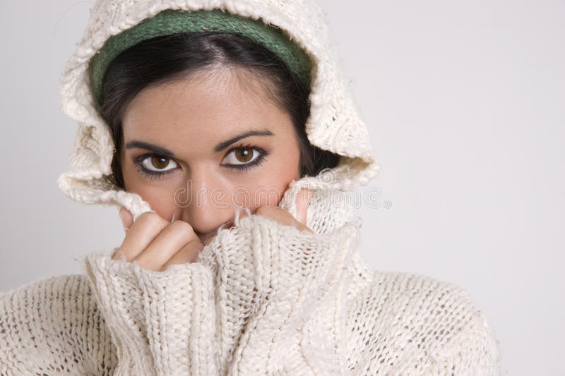 Attractive Woman Covering Half Her Face with Sweater royalty free stock photography