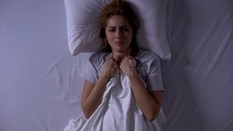 Attractive woman crying lying in bed at night, female weakness and fragility royalty free stock image