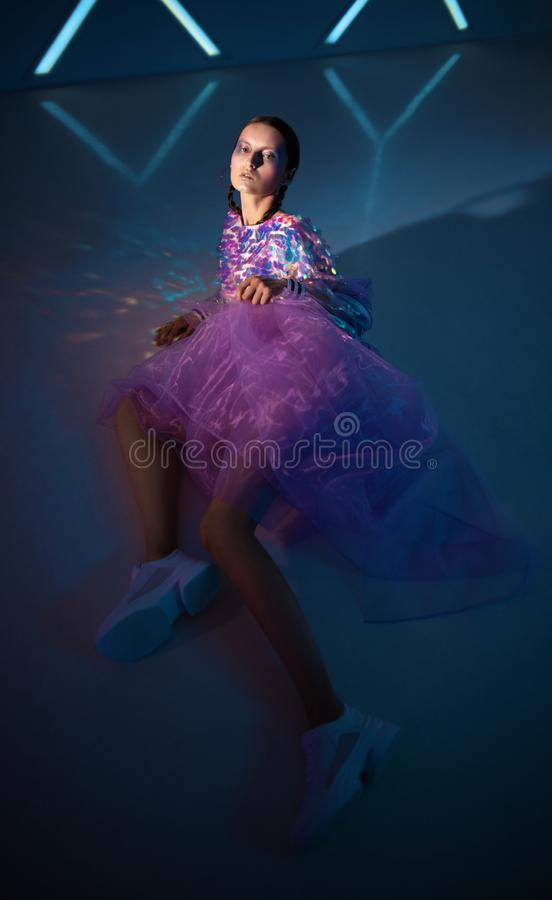 Attractive woman in disco style clothes. Posing on dark blue background royalty free stock photography