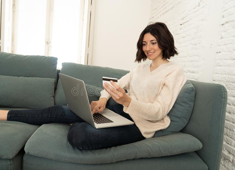 Happy young woman sitting with laptop and a credit card shopping online at home royalty free stock photos