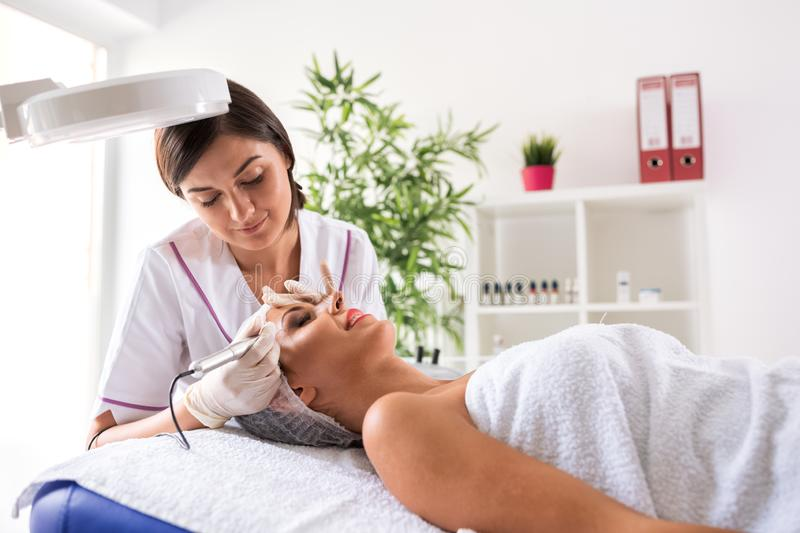 Attractive woman doing permanent makeup treatment. Attractive women doing permanent makeup treatment in a beauty salon royalty free stock photography