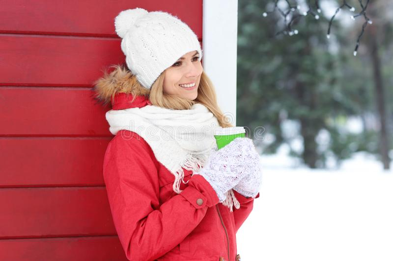 Attractive woman drinking coffee outdoors. On winter day stock photography