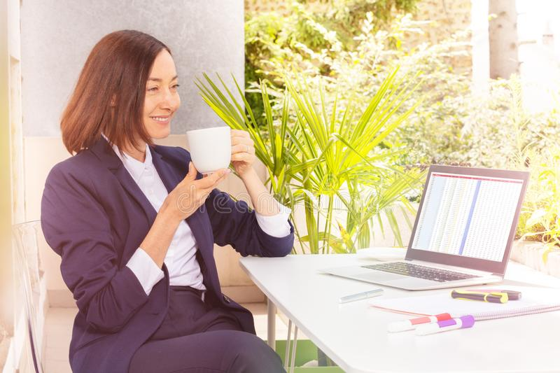 Attractive woman drinking coffee, working at cafe stock photos
