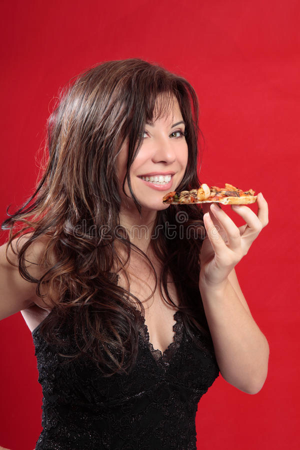 Attractive woman eating pizza. Attractive woman with long brown hair eating a slice of pizza and smiling. Red background stock image