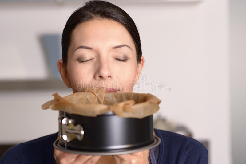 Attractive woman enjoying aroma of freshly baked cake royalty free stock photography