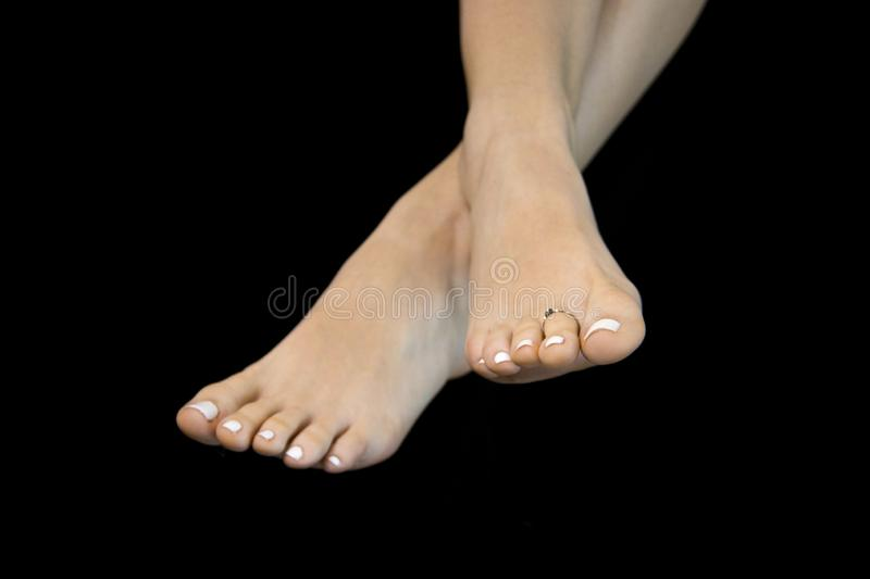 Beautiful feet of woman, crossed in diagonal on black abstraction background, isolated feet, close up, delicate well-kept foot. Attractive woman feet crossed in royalty free stock photos