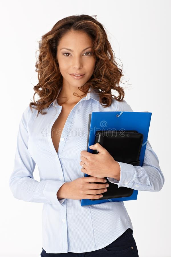 Attractive woman with folders. Attractive young woman holding folders, standing over white background stock image