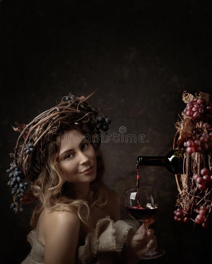 Attractive woman with glass of red wine in wine cellar . Vine wreath with blue grapes on a head. Red wine is poured from a bottle royalty free stock images