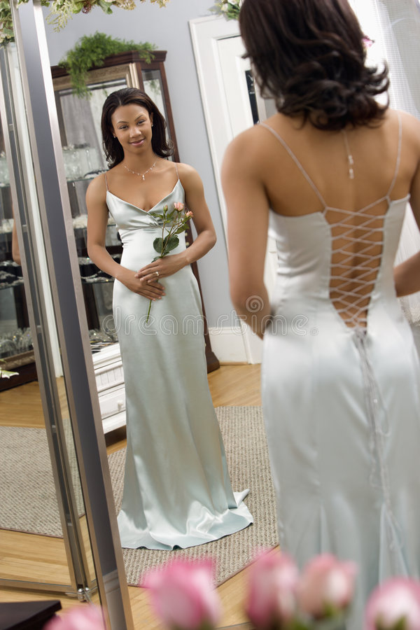 Attractive woman in gown. Portrait of an African-American woman in a elegant evening gown looking in mirror stock photo