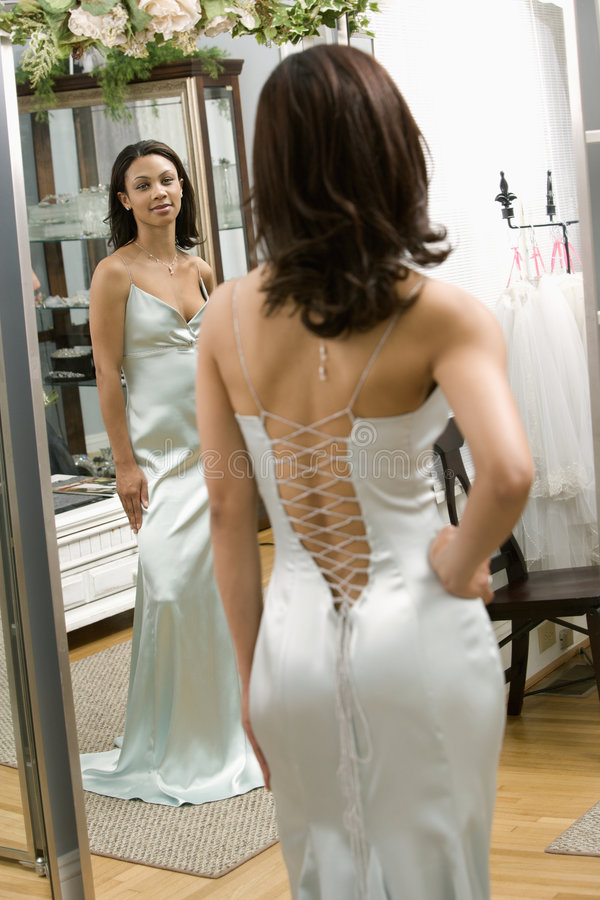 Attractive woman in gown. Portrait of an African-American woman in a elegant evening gown looking in mirror royalty free stock image