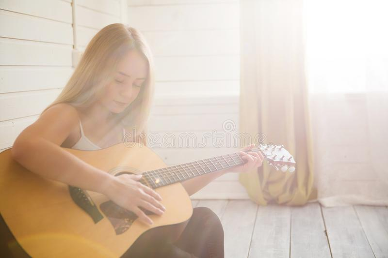 Attractive woman with guitar sitting in light room with wooden floor. Musician, concert, hobby, leisure, rehearsal concept stock images