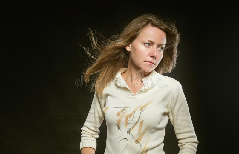 Attractive woman with hair fluttering in the wind on black background. Calm and even-tempered girl in beige jacket looks stock photo