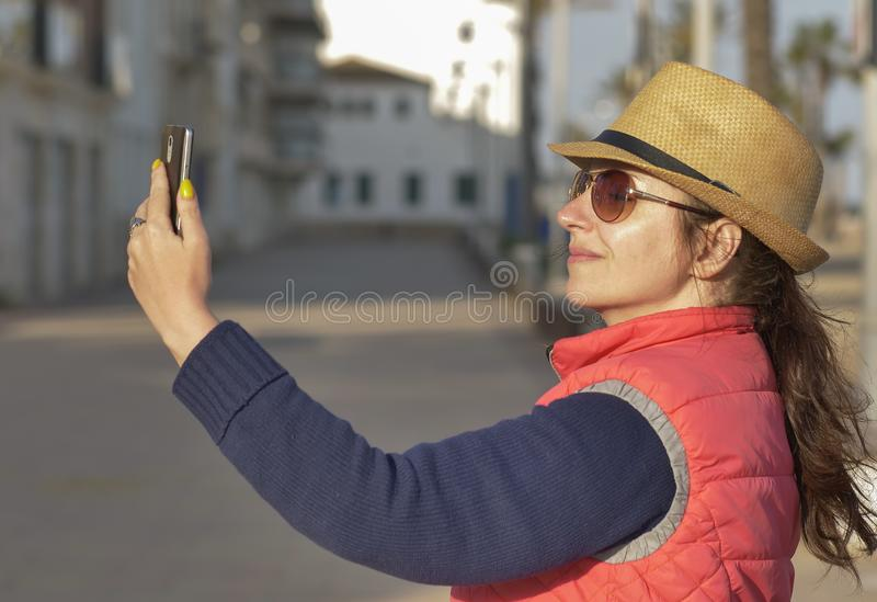 Attractive young woman in hat and glasses takes a selfie on a sunny autumn day stock photography