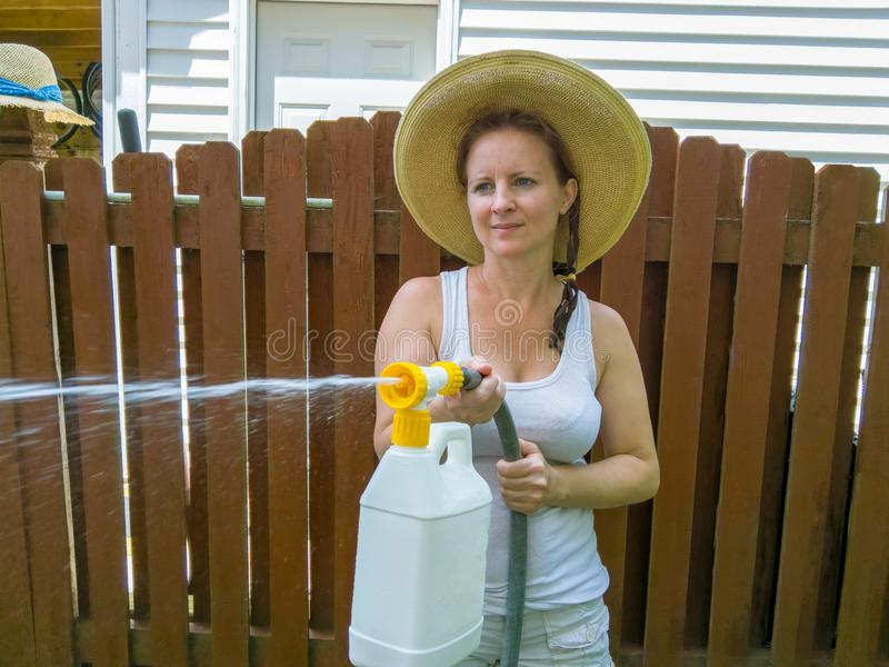 Attractive woman in a hat using a pressure sprayer stock image