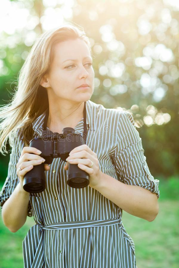 Attractive woman having binoculars outdoor in nature stock photo