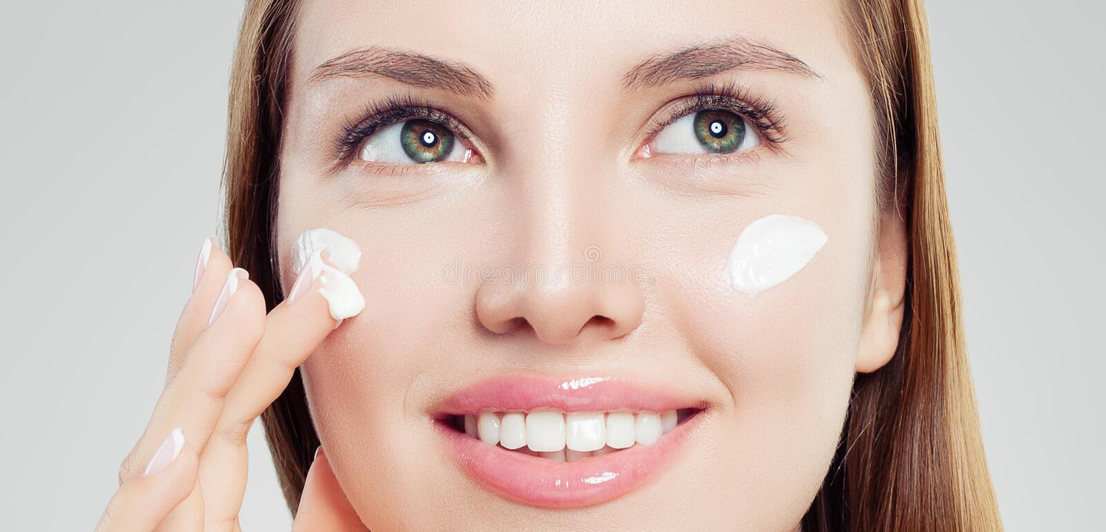 Attractive woman with healthy skin applying cosmetic cream, face closeup. Skincare, beauty and facial treatment concept royalty free stock photography