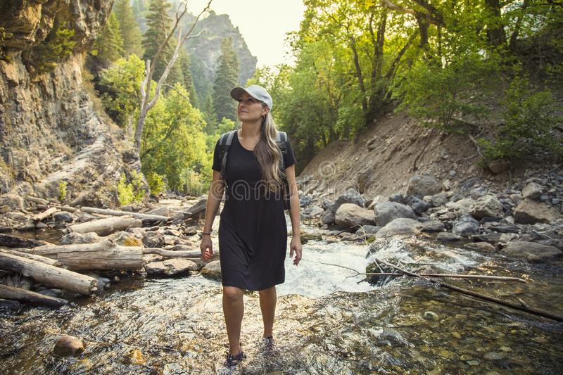 Attractive Woman hiking across a mountain stream on a hike stock photos