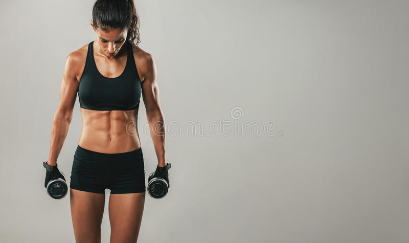 Attractive woman holding dumbbells facing downward. As if to prepare mentally for an intense workout over gray background with copy space royalty free stock images