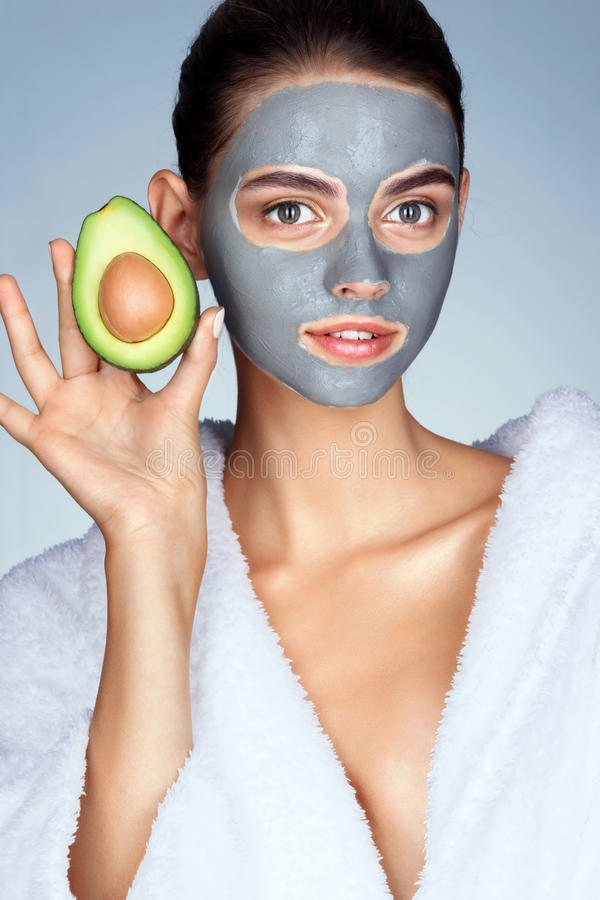 Attractive woman holding half an avocado in hand. stock images
