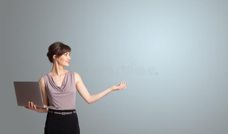 Attractive woman holding a laptop with copy space royalty free stock photography