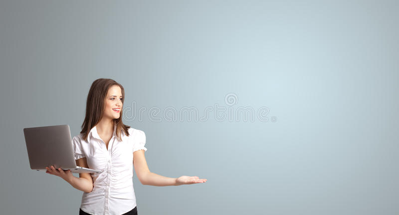Attractive woman holding a laptop with copy space royalty free stock photo