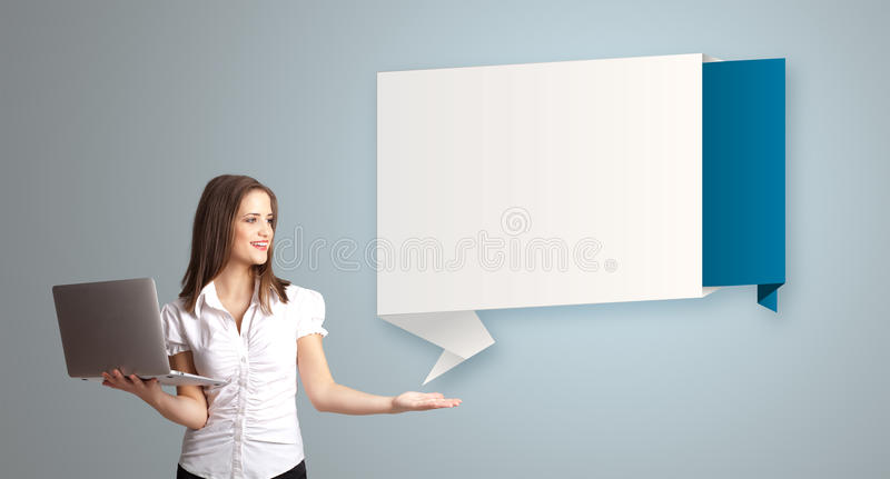 Attractive woman holding a laptop and presenting modern origami royalty free stock photos