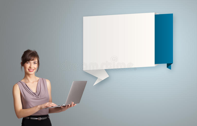 Attractive woman holding a laptop and presenting modern origami royalty free stock photography