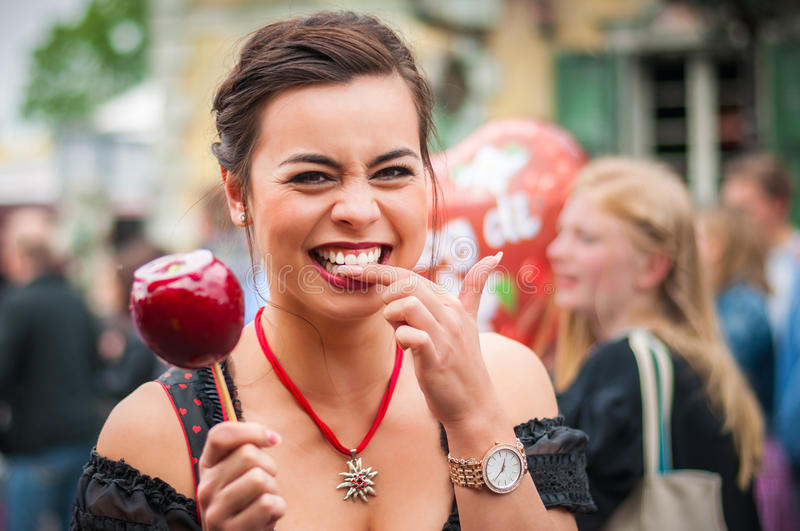 Attractive woman holding a red caramelized apple royalty free stock image