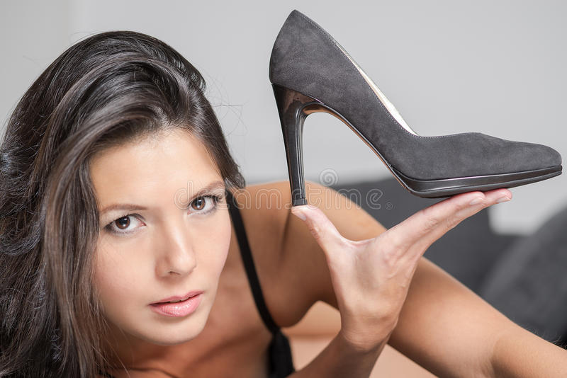 Attractive woman holding up an elegant shoe royalty free stock image