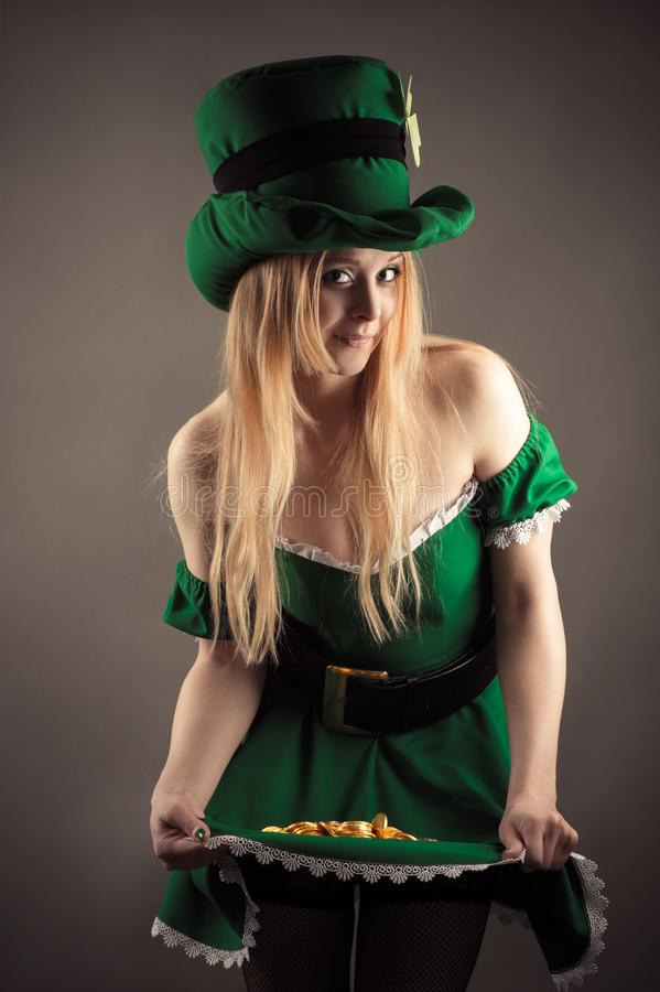 Attractive woman in image leprechaun with coins in skirt royalty free stock photos