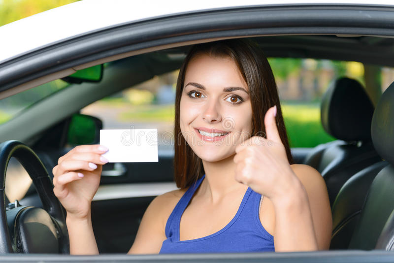 Attractive woman inside car showing card stock image