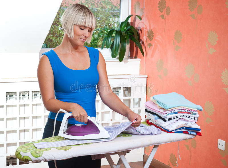Attractive woman ironing royalty free stock photography