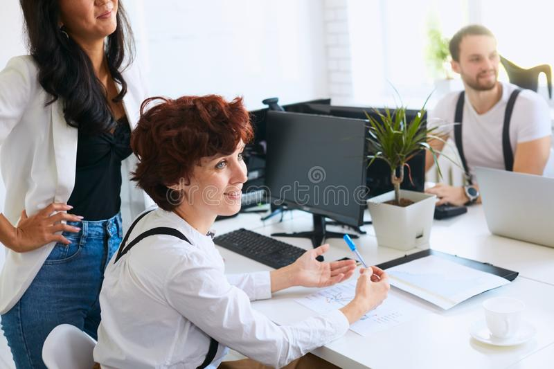 Attractive woman listen to teacher or mentor coach speaking. Beautiful smiling women look side at coach, attentively listen to speaking,colleagues around her stock photography