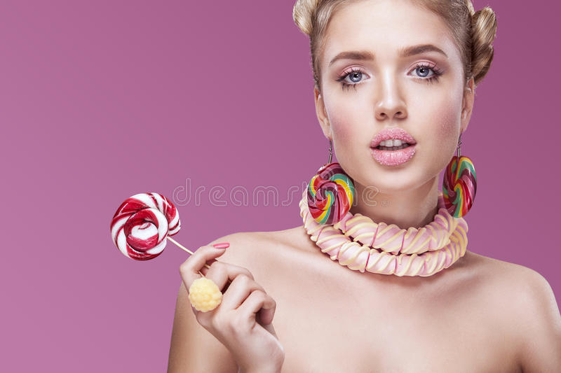 Attractive woman with lollipop in hand on pink background. Young woman with candy on pink bakground royalty free stock photo