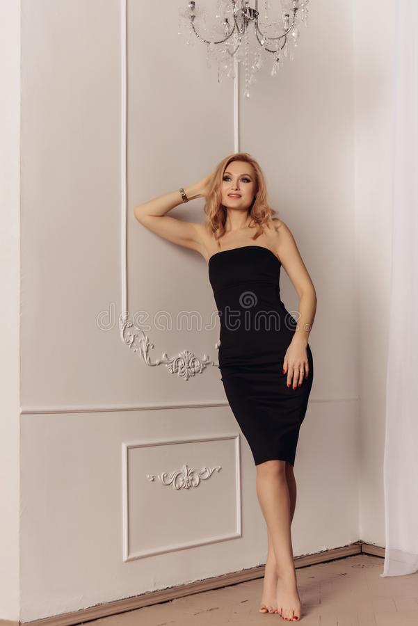 Attractive woman with long blonde hair dressed in fashionable black midi dress with short. royalty free stock photos