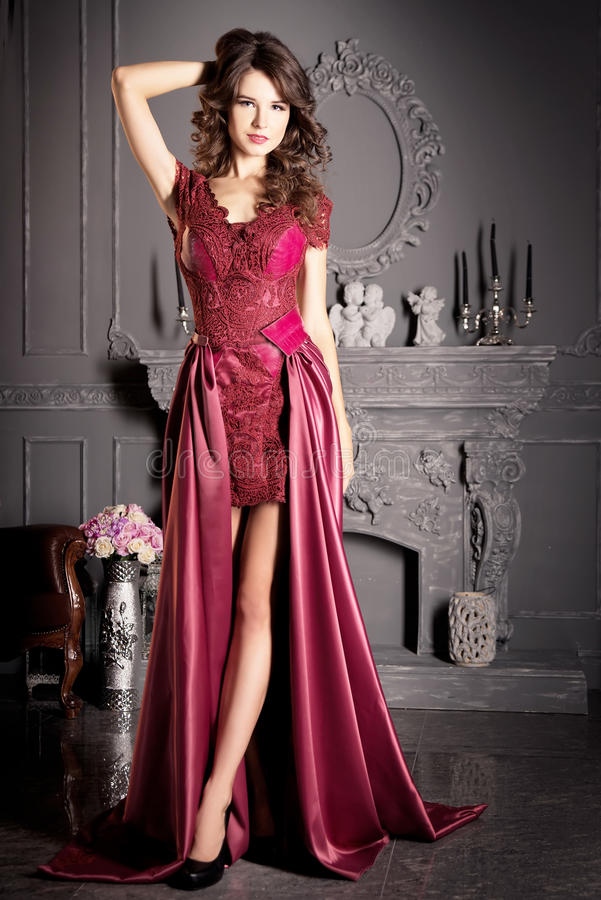 Attractive woman in long claret lace dress. Indoor stock image