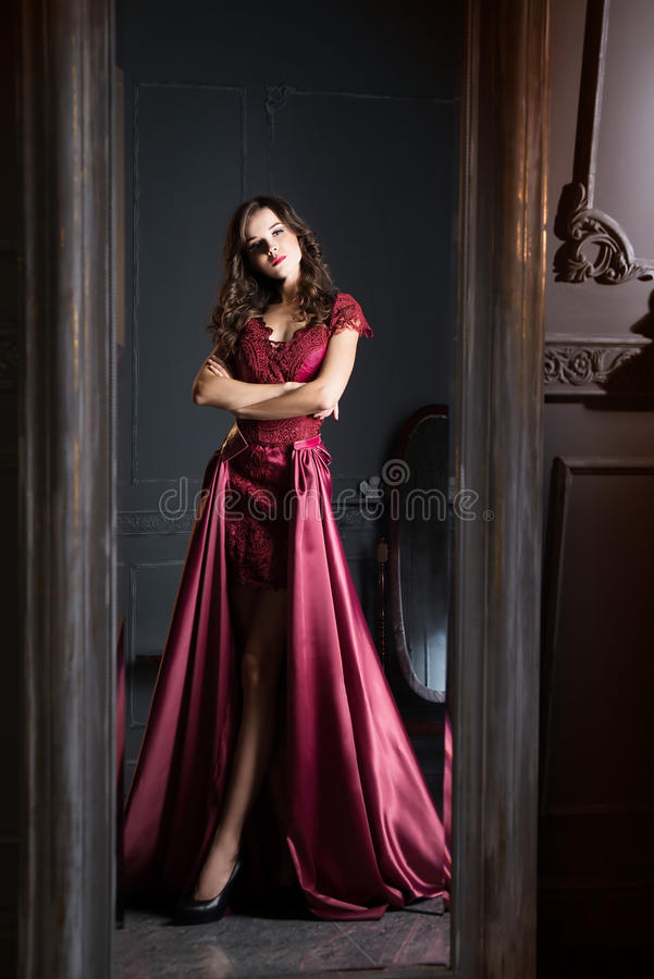 Attractive woman in long claret lace dress. Reflected in mirror. Indoor royalty free stock image