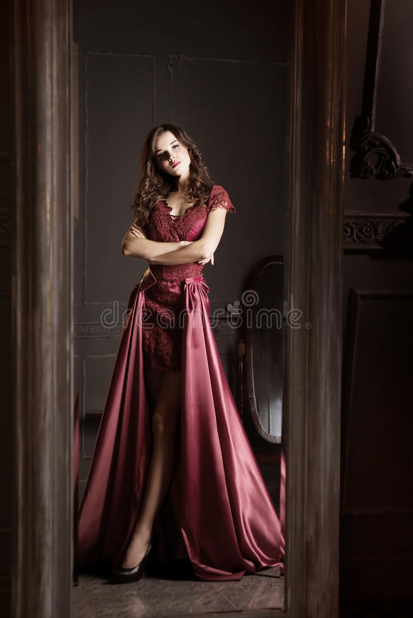 Attractive woman in long claret lace dress. Reflected in mirror. Vintage royalty free stock image