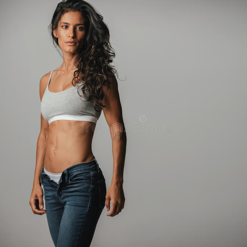 Attractive woman with long hair wearing jeans. And halter top standing in a gray room royalty free stock photography