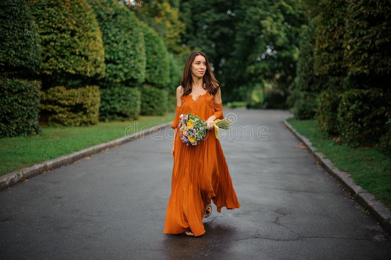 Attractive woman in orange dress walking on the road with bouquet of flowers stock images