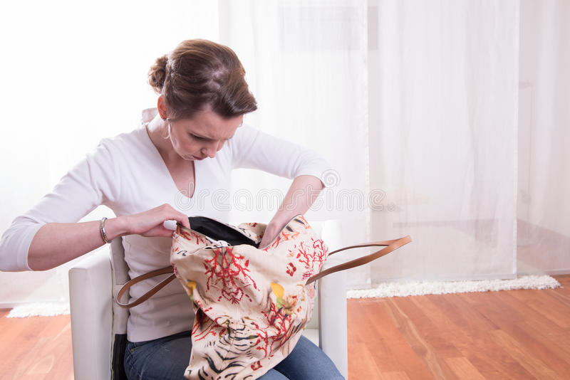 Attractive woman looking into bag.  stock photography