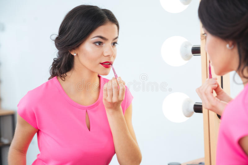 Attractive woman looking at mirror and applying red lipstick tolips royalty free stock photography