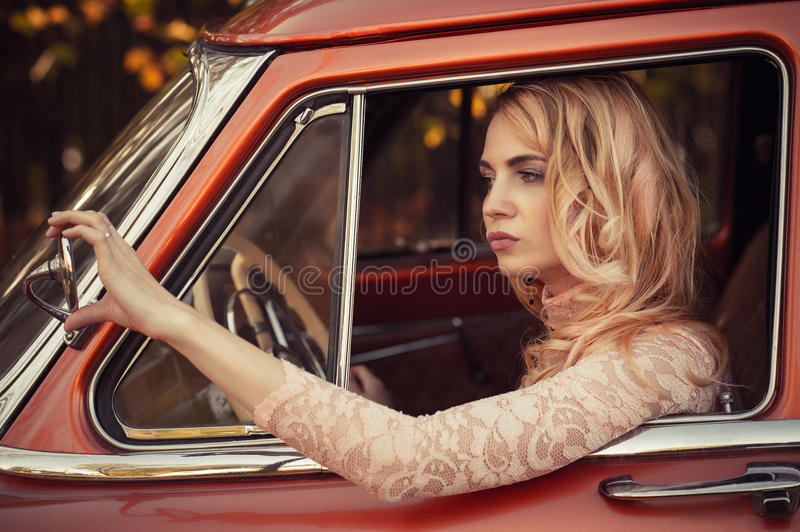 Attractive woman looking at the side mirror retro car royalty free stock images