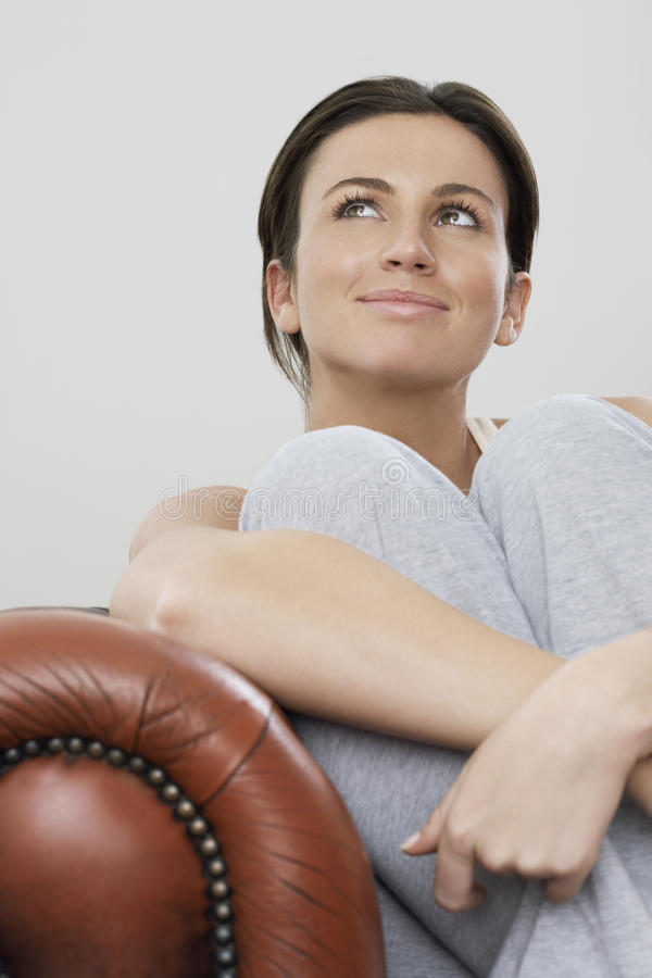 Attractive Woman Looking Up While Sitting On Sofa royalty free stock photo