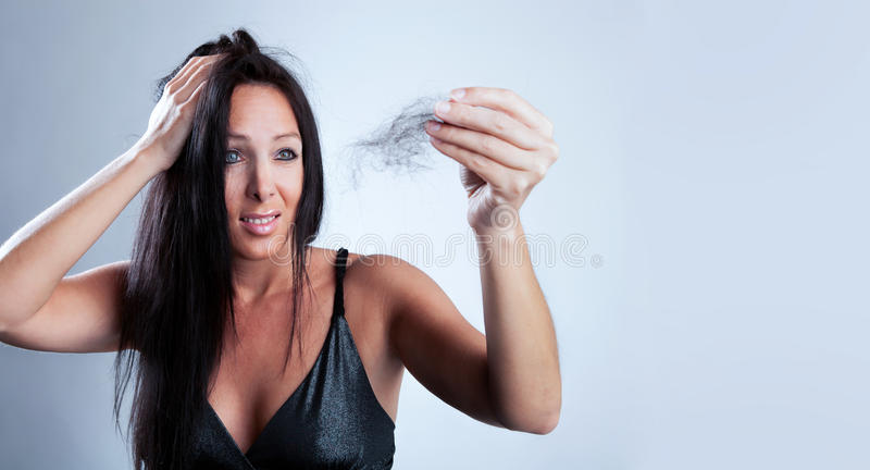 Attractive woman looks shocked to her lost hair stock image
