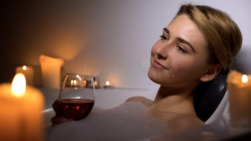 Attractive woman lying in bath with foam bubbles and candles, drinking wine royalty free stock photography