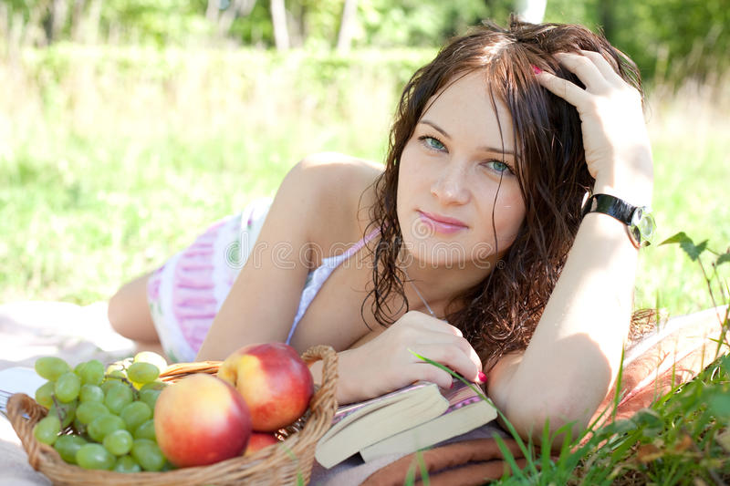 Attractive woman lying on the grass royalty free stock photos