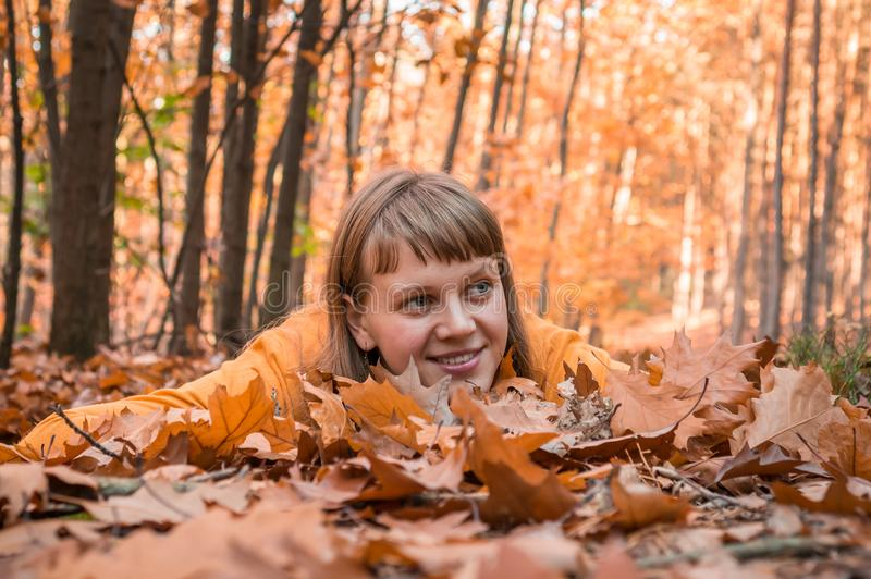 Attractive woman is lying over autumn leaves in park royalty free stock photos