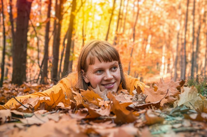 Attractive woman is lying over autumn leaves in park stock photos