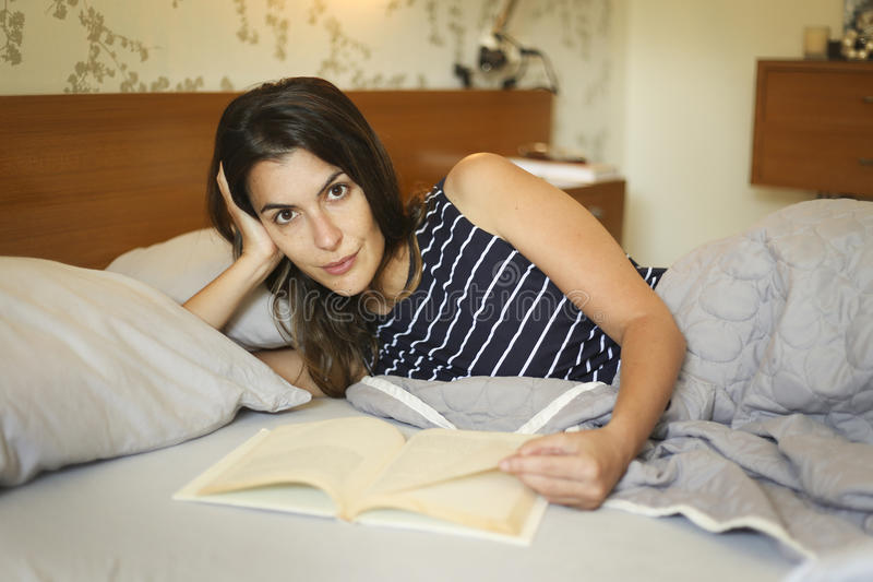 Attractive woman lying reading in bed stock photography